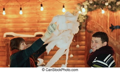 A guy and a girl throw artificial snow and hug against the backdrop of a fairy-tale house. Christmas and New Year theme.