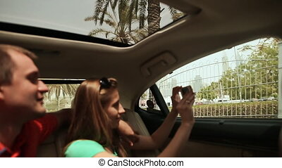 A guy and a girl travel in Dubai by car and admire the city.