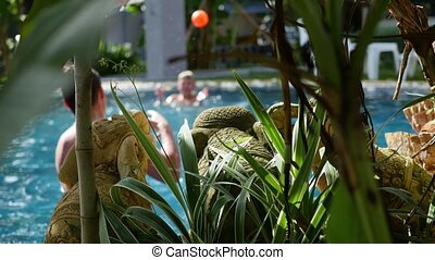 a guy and a kid playing ball in the pool. sports outdoors