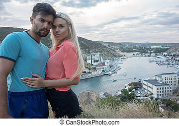 A guy and his girlfriend stand on the edge of a cliff hugging each other by the waist in the background you can see the Balaklava Bay in Crimea