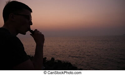 A guy at sunset smokes a e-cigarette. Vape. Vapping....