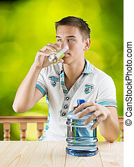 a guy drinking water from glass