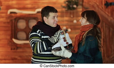 A guy gives his white skates to his girlfriend, which she is very happy about against the background of a magical fairy-tale house. Christmas and New Year theme.