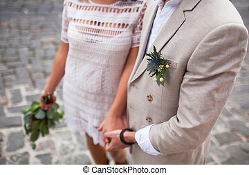 A guy holding a girl by the hand with a bouquet of flowers