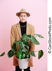 A guy in a hat and coat is holding a pot with a house plant