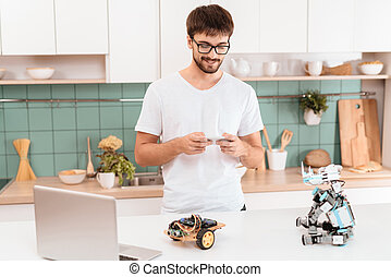 A guy in glasses stands in the kitchen and holds a smartphone in his hands. He controls the robot with a smartphone.