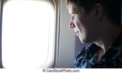 A guy looks out the window of a plane on a sunny day