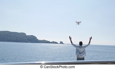 A guy on a yacht on the sea launches a drone. A drone flies...