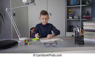 A guy schoolboy is dressed in a dark blue shirt sitting at the table at home and doing a homework. Books and notebooks are on the table
