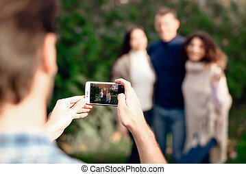 A guy takes pictures of friends on a smartphone.