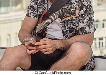 A guy with a beard playing guitar at home