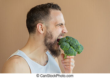 A guy with a beard sniffs broccoli