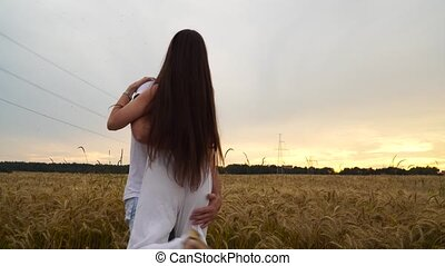 A guy with a girl in his arms is spinning in a wheat field at sunset