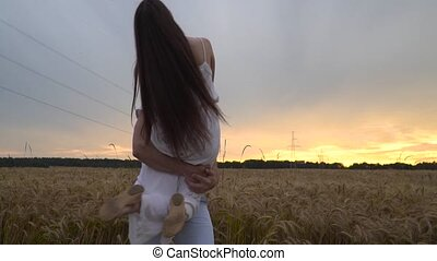 A guy with a girl in his arms is spinning in a wheat field at sunset. Slow motion