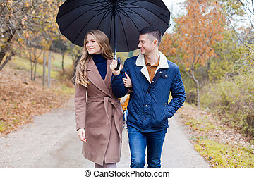 a guy with a girl in the Park of autumn rain umbrella