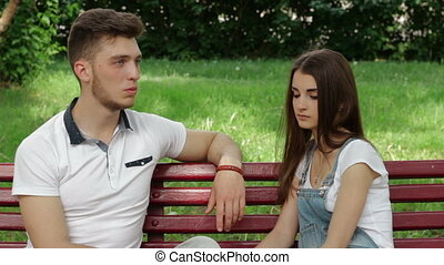 a guy with a girl sitting on a bench and talk