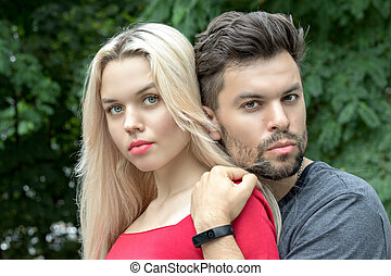 A guy with a stubble on his face, gently hugs his girlfriend by the shoulders