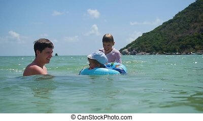 a guy with kids plays having fun in the sea