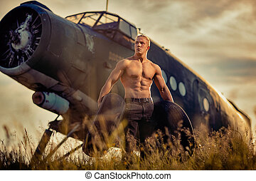 A guy with tires in his hands is standing by the plane.