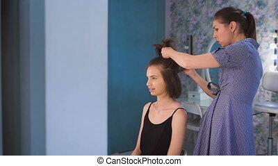 A hair stylist preparing a pretty bride before the wedding...