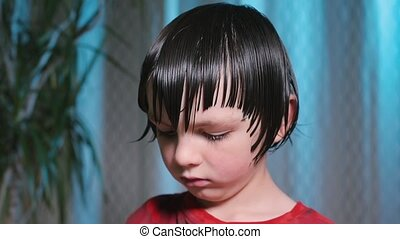 A hairdresser cuts the hair of a boy on his head.