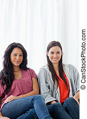 A half length-shot of two smiling women sitting on the couch while looking into the camera