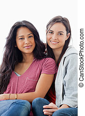 A half length shot of two women on the couch looking towards the camera while they both smile