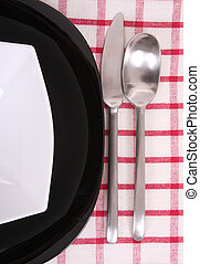 A half of black and white plate with utensils