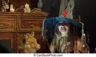 A Halloween witch strokes a dead fox and smiles wickedly and...