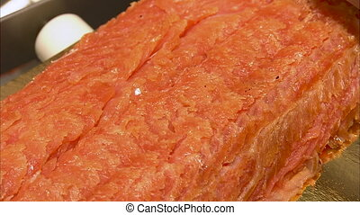 A ham sliced shot - A medium shot of a ham getting sliced by...