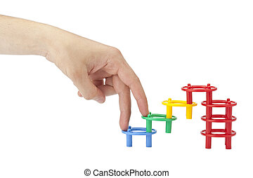 a hand climbing on the plastic building toys