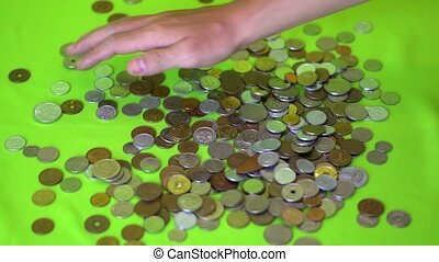 A hand grabs a lot of international coins and slides it...