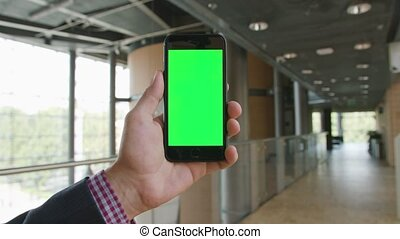 A Hand Holding a Phone with a Green Screen - Lublin, Poland...