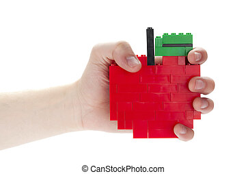 a hand holding apple made of lego blocks