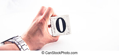 A hand holding digit number 0 (zero) on white background
