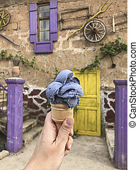 A hand holding ice cream made with lavender