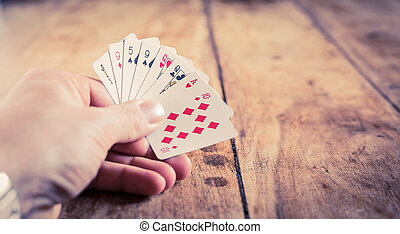 A hand holding playing cards on o vintage wooden table | Gambling | Gambler