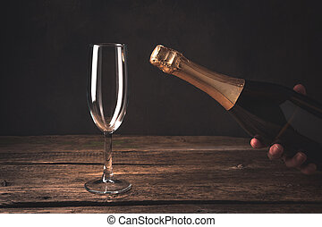 A hand holds a closed champagne bottle next to an empty wine glass on a wooden background.