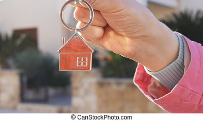 A hand is holding a key from the new home