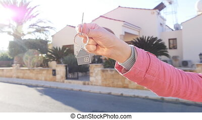 A hand is holding a key from the new home. Real estate...