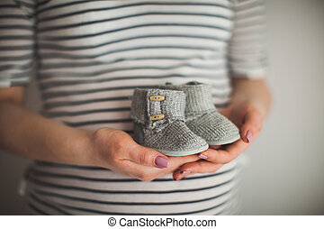 A hand is holding a pair of little shoes. It's a shoes for infant on gray background. Mother and baby theme. pregnant woman.