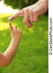 hand of parent and child in nature