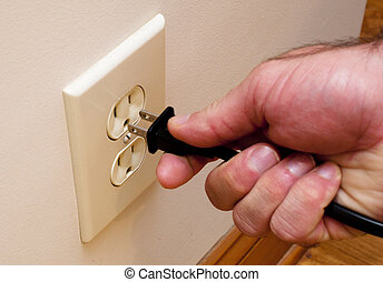 A hand plugging a plug into an electrical outlet.