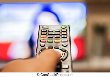 A hand pressing a television remote control button
