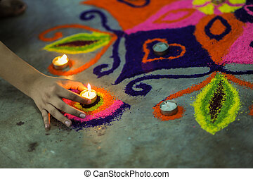 A hand putting a lamp on a beautiful and colorful rangoli on Diw