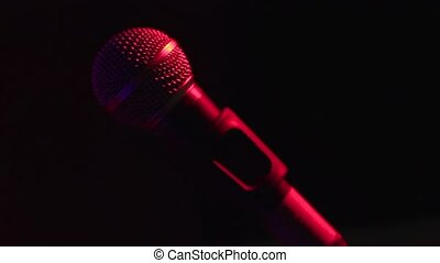 A hand touches to the microphone on the stage rap of concert...