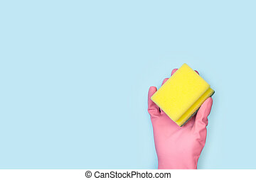 A hand with a pink rubber glove holding a cleaning sponge