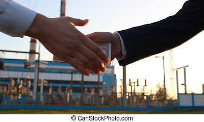 A hand with money dollars against a power plant background...