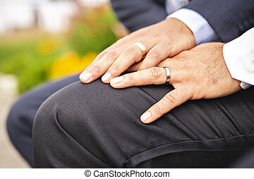 A hand with ring of gay couple in the park on their wedding...