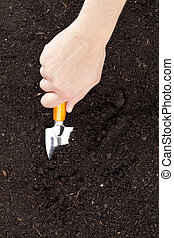 a hand with shovel cultivating the soil